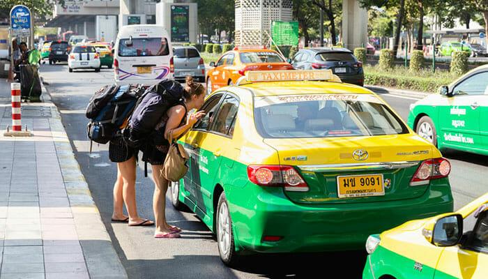 バンコクのタクシー運転手と話すバックパッカー